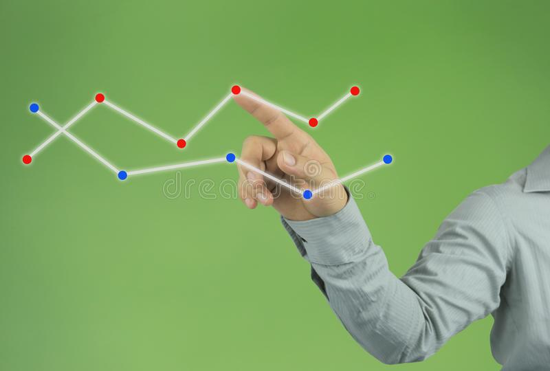 mano del hombre de negocios que señala a la línea superior de un gráfico en vagos verdes imagen de archivo