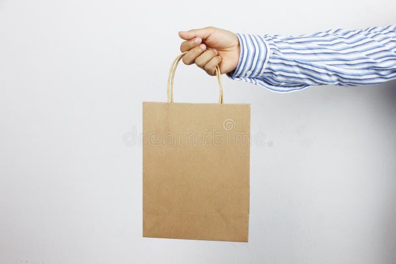 Mano del hombre de negocios que sostiene la bolsa de papel marrón foto de archivo
