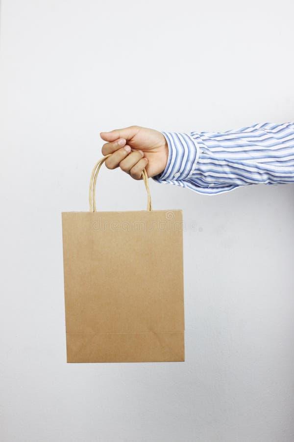 Mano del hombre de negocios que sostiene la bolsa de papel marrón imagen de archivo libre de regalías