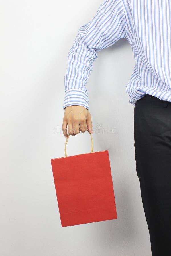 Mano del hombre de negocios que sostiene la bolsa de papel roja fotografía de archivo libre de regalías