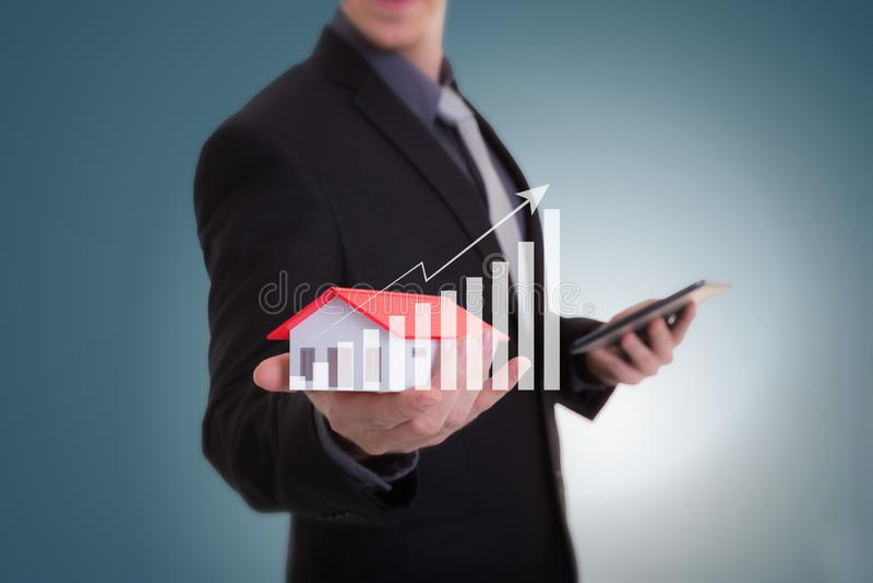 Mano del hombre de negocios que sostiene la casa que representa la casa en propiedad y t imagen de archivo