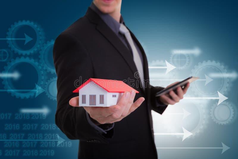 Mano del hombre de negocios que sostiene la casa que representa la casa en propiedad y t fotografía de archivo
