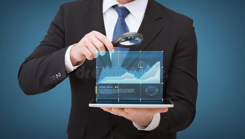 Mano del hombre de negocios que sostiene la lupa sobre la PC de la tableta fotos de archivo libres de regalías