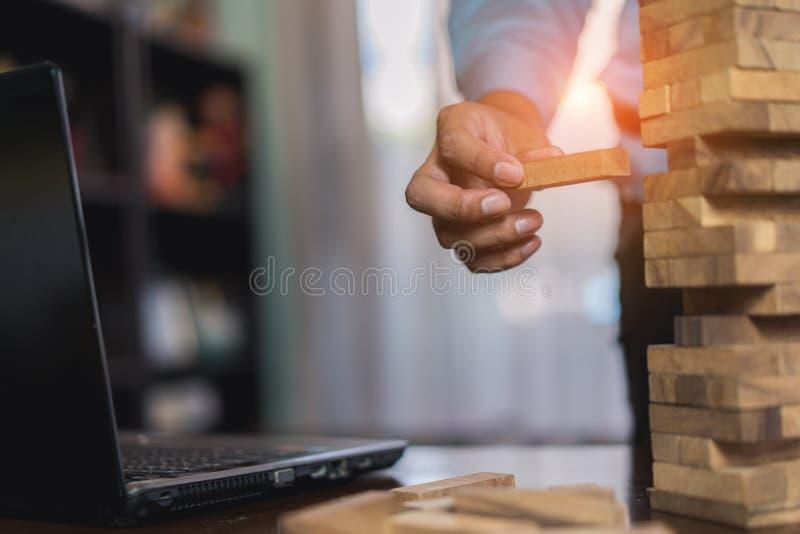 Mano del hombre de negocios que tira del bloque de madera antes de fall en torre del edificio imagen de archivo libre de regalías