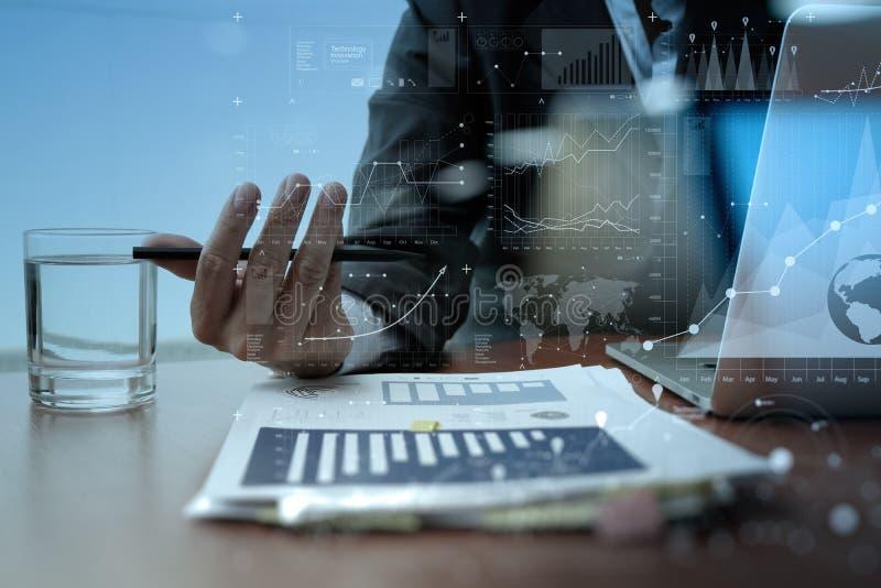 Mano del hombre de negocios que trabaja en el ordenador portátil con capa digital foto de archivo
