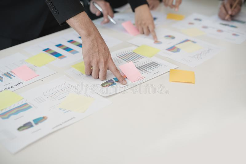 Mano del hombre de negocios y de la mujer de negocios que trabajan en cartas de los datos, d imagen de archivo libre de regalías