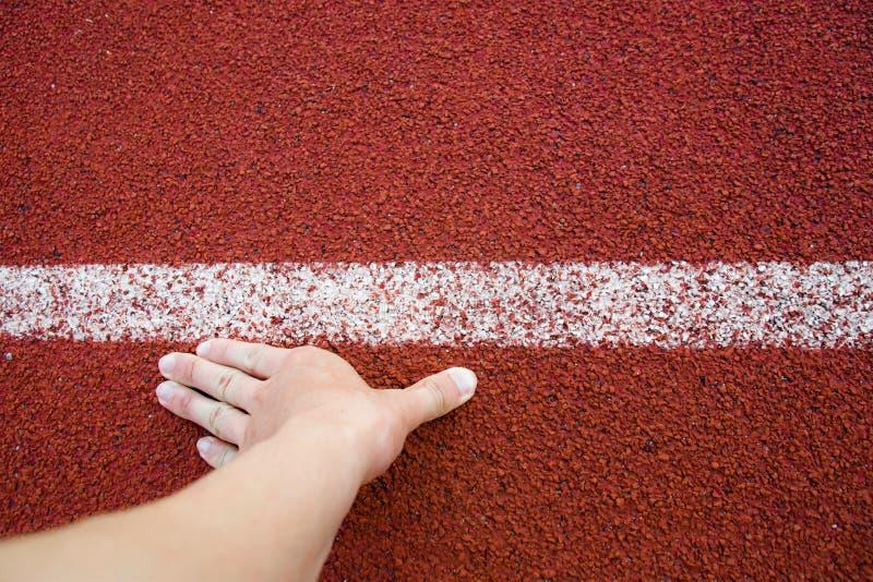 Mano del hombre del corredor de la visión superior en las líneas blancas de la pista de la posición de comienzo que corren en el  imágenes de archivo libres de regalías
