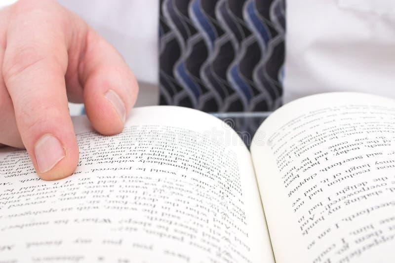 Mano del hombre en el libro abierto imagen de archivo