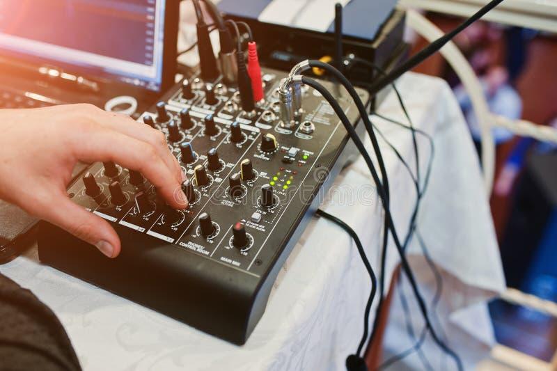 Mano del hombre en la consola de mezcla digital Panel de control del mezclador de sonidos fotografía de archivo