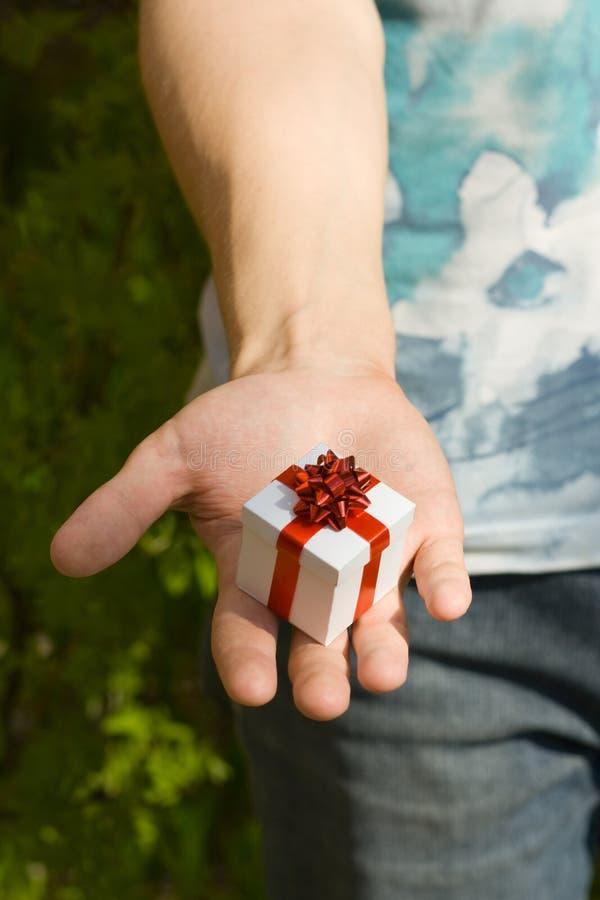 Mano del hombre joven con el regalo fotografía de archivo libre de regalías