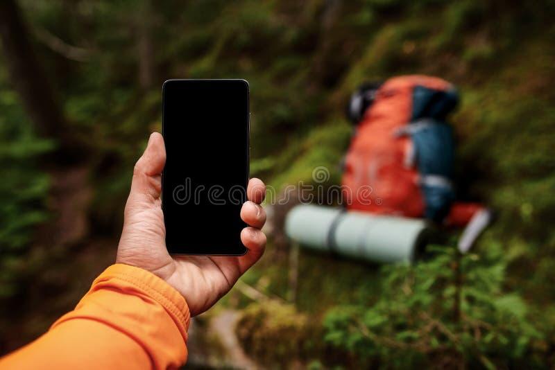 Mano del hombre joven, que se está colocando en la roca y está sosteniendo el teléfono elegante imagenes de archivo