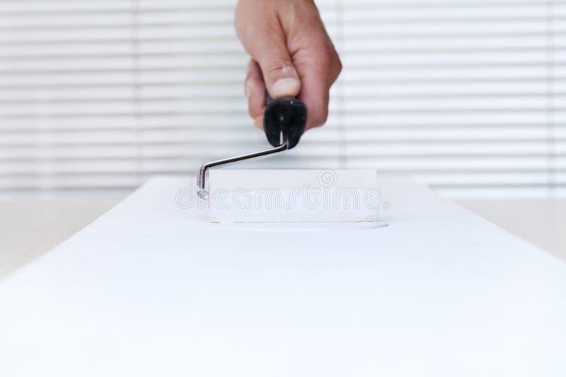 Mano del hombre del pintor con el rodillo de pintura, pintando en la parte posterior del tablero blanco imagen de archivo libre de regalías
