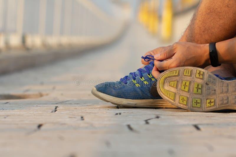 Mano del hombre que ata cordones de zapato del deporte en ropa casual después de entrenamiento Hombre joven de la aptitud que cor imagen de archivo libre de regalías