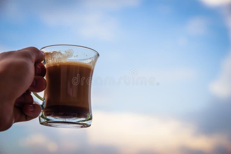 Mano del hombre que aumenta el vidrio con café de la mañana Comenzar un concepto del buen día Con el cielo nublado en el fondo imagen de archivo