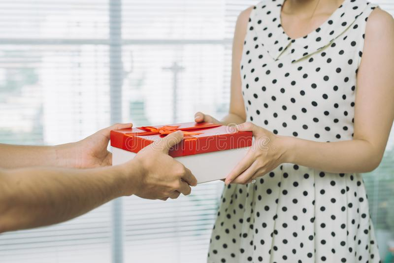Mano del hombre que da el regalo rojo a la mujer fotografía de archivo