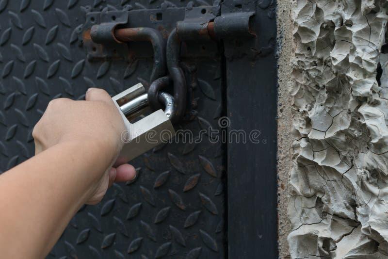 Mano del hombre que está sosteniendo un candado del metal con el cual se abroche foto de archivo