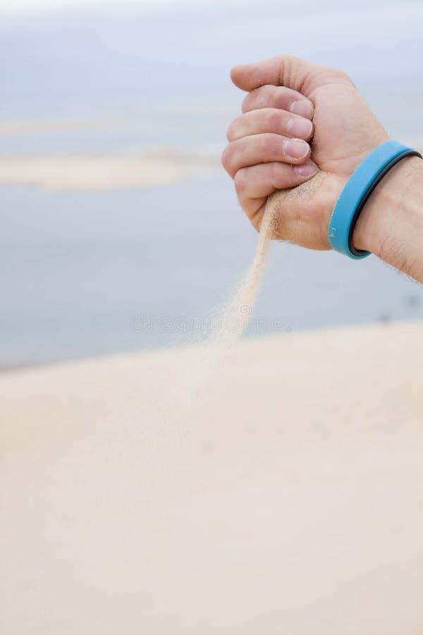 Mano del hombre que lanza la arena sobre una playa fotos de archivo libres de regalías