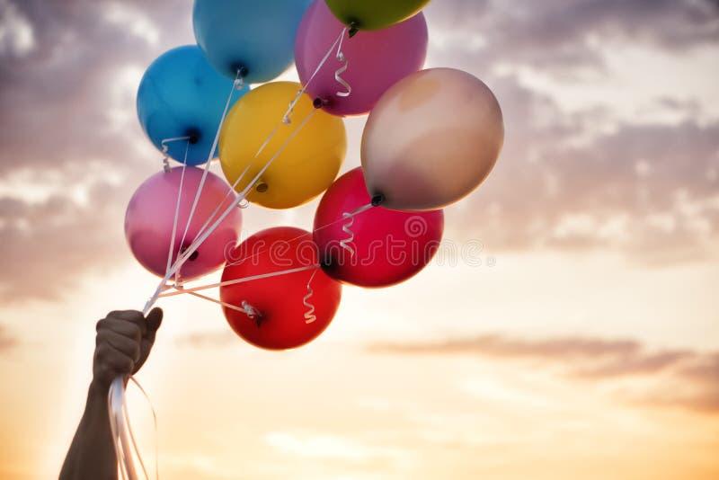 Mano del hombre que lleva a cabo globos coloridos y una puesta del sol hermosa Globos de la fiesta de cumpleaños imagen de archivo libre de regalías