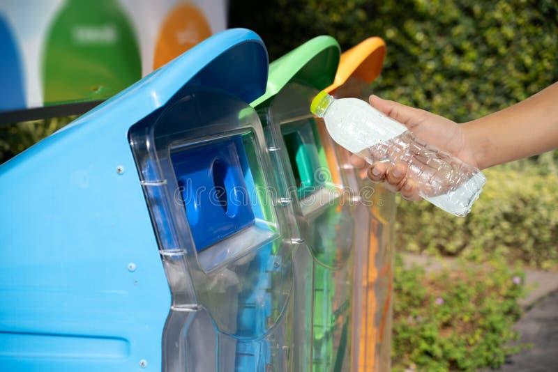 mano del hombre que pone la reutilización plástica para reciclar el ambiente del concepto fotografía de archivo