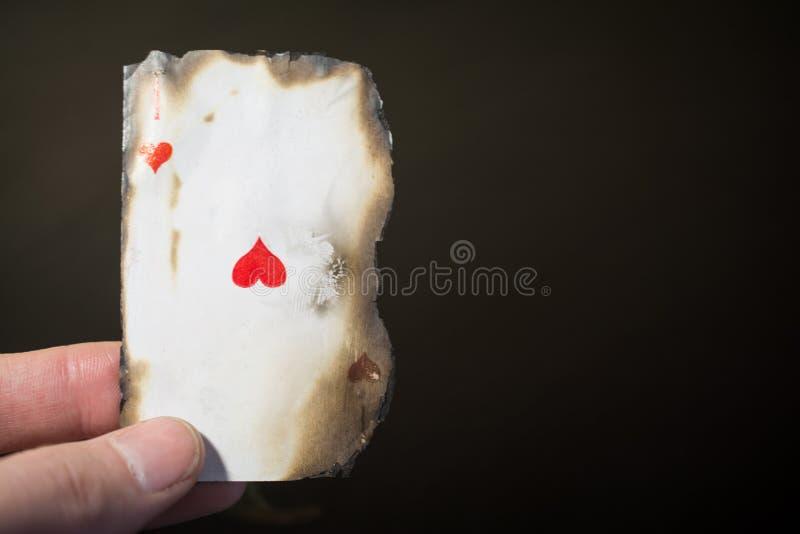 Mano del hombre que sostiene el as del cierre abstracto del naipe del fondo de los corazones para arriba en un fondo negro imágenes de archivo libres de regalías