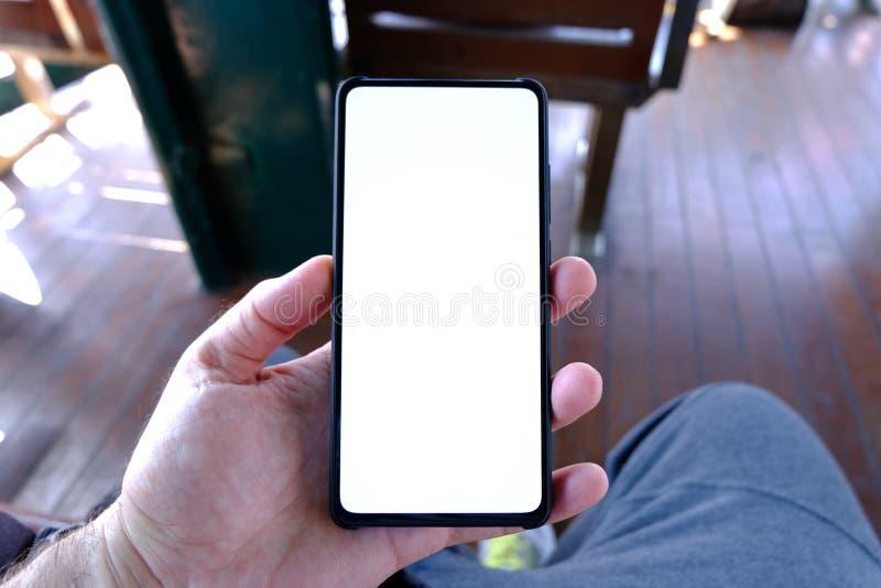 Mano del hombre que sostiene el smartphone negro con la pantalla en blanco y el marco moderno menos dise?o fotografía de archivo libre de regalías