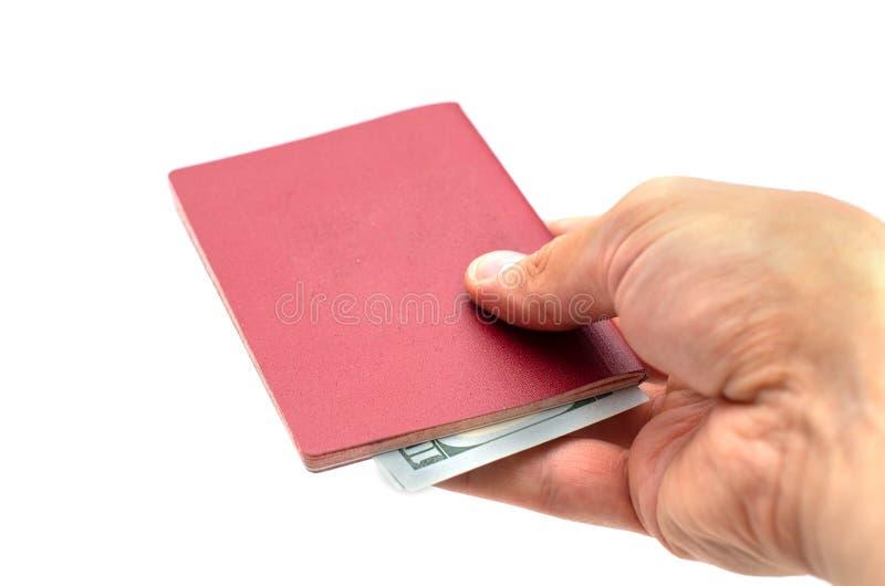Mano del hombre que sostiene hacia fuera un pasaporte con el dinero fotos de archivo