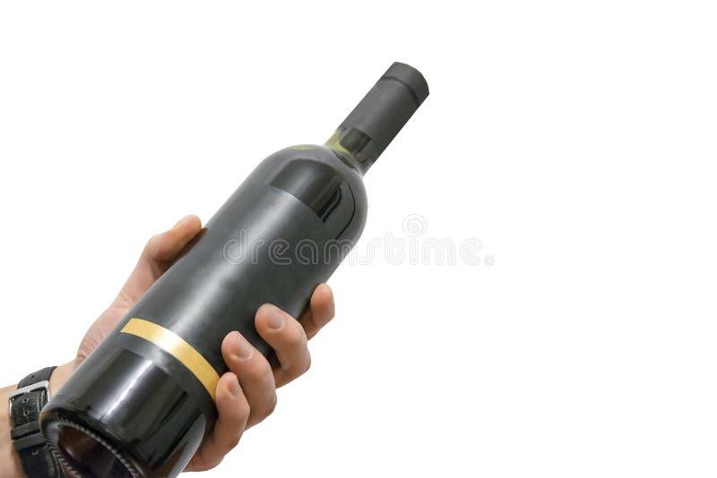 Mano del hombre que sostiene la botella de vino con la etiqueta de la plantilla aislada en el fondo blanco imágenes de archivo libres de regalías