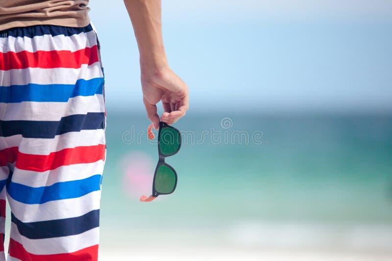 Mano del hombre que sostiene las gafas de sol en la playa fotografía de archivo