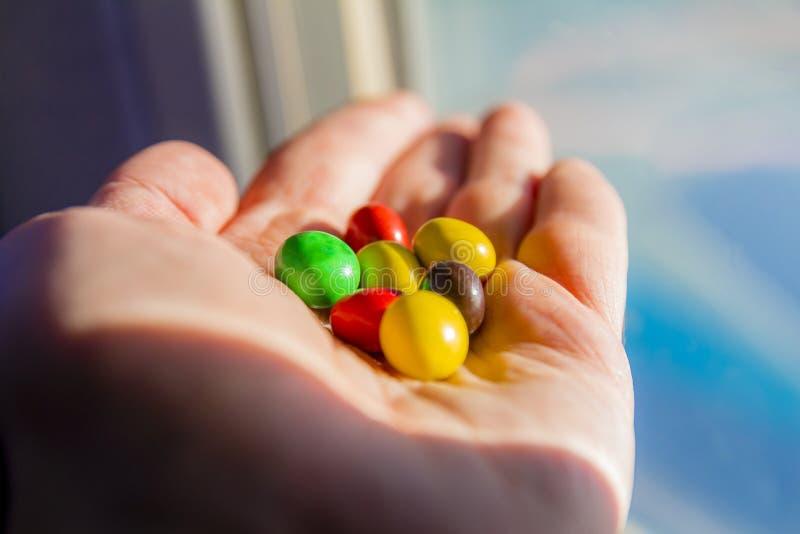 Mano del hombre que sostiene los botones coloridos de los caramelos de chocolate imagen de archivo libre de regalías