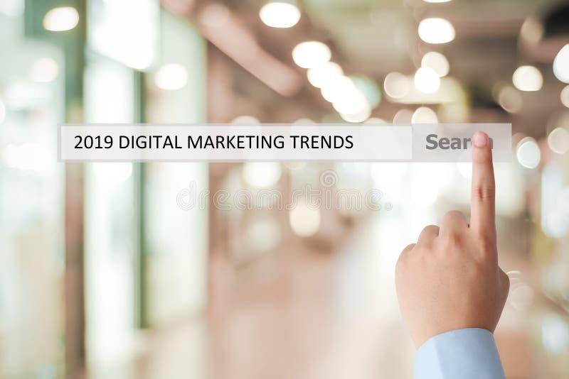 Mano del hombre que toca 2019 tendencias de comercialización digitales en barra de la búsqueda sobre el fondo de la oficina de la fotos de archivo
