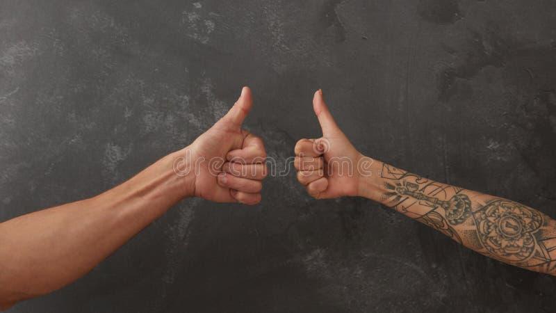 Mano del hombre y mano femenina con el tatuaje imagen de archivo
