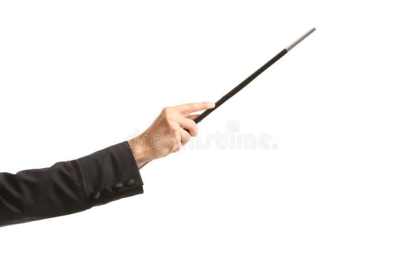 Mano del ilusionista con la vara mágica en el fondo blanco fotografía de archivo