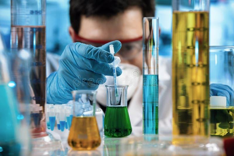Mano del ingeniero químico que mide con una pipeta muestras con la pipeta de la jeringuilla en el laboratorio de investigación imagenes de archivo