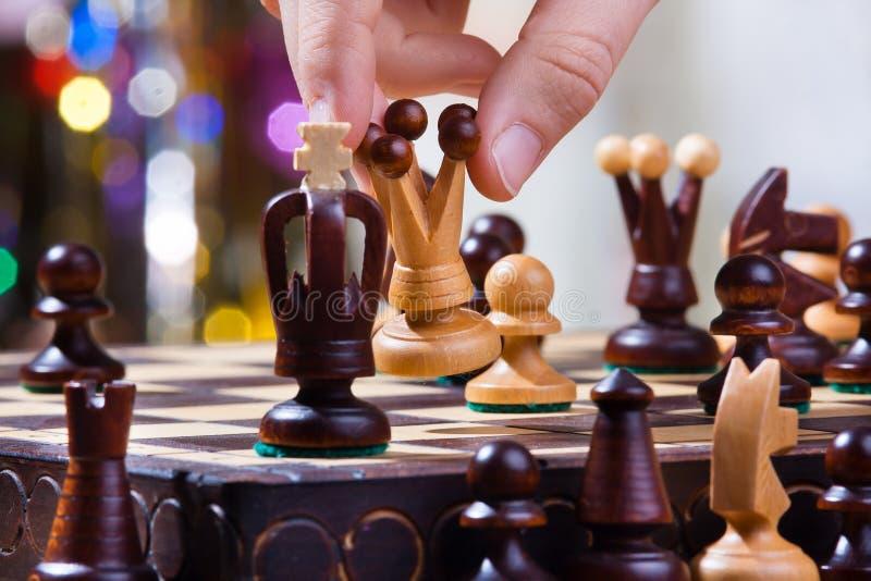 Mano del jugador de ajedrez con la reina fotografía de archivo libre de regalías