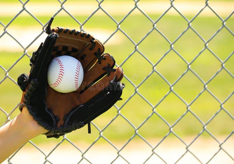 Mano del jugador de béisbol con el guante y de la bola sobre campo fotografía de archivo libre de regalías
