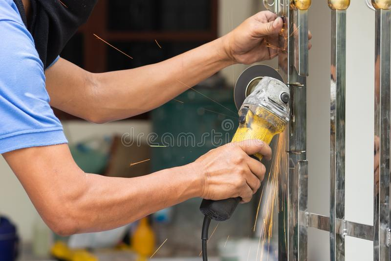 Mano del lavoratore che funziona dallo strumento elettrico di industria della smerigliatrice che taglia st fotografie stock