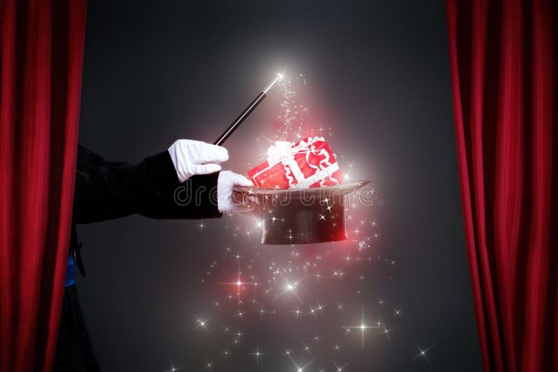Mano del mago con la vara mágica que hace el regalo de la Navidad fotos de archivo