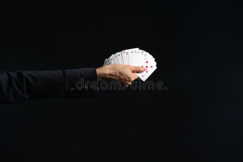 Mano del mago que sostiene tarjetas en fondo oscuro foto de archivo libre de regalías