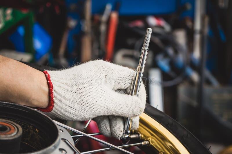 Mano del mecánico que comprueba la presión de aire con el indicador de presión de neumáticos imagenes de archivo