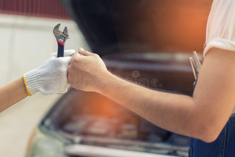Mano del mecánico que comprueba y que fija un coche quebrado en garaje mano o imagenes de archivo