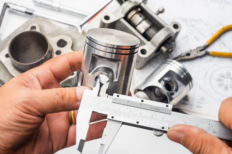 Mano del mecánico que detiene a Vernier Caliper Measurements en el mot fotos de archivo libres de regalías