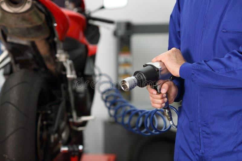 Mano del mecánico que sostiene un arma neumático imagen de archivo libre de regalías