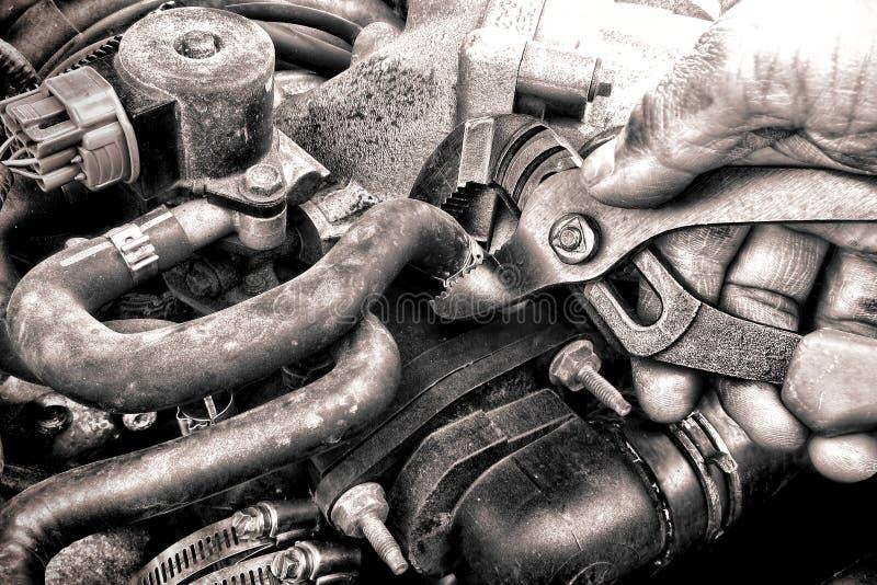 Mano del meccanico di riparazione automatica che ripara una parte di motore dell'automobile fotografia stock