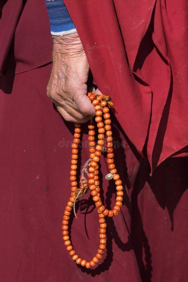 Mano del monje que sostiene el rosario imagenes de archivo