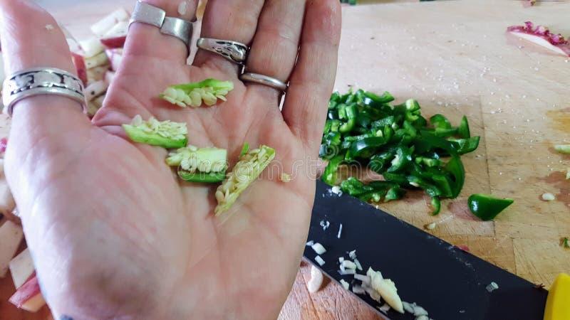 Mano del ` n de la mujer que muestra el innards del jalapeno imagenes de archivo
