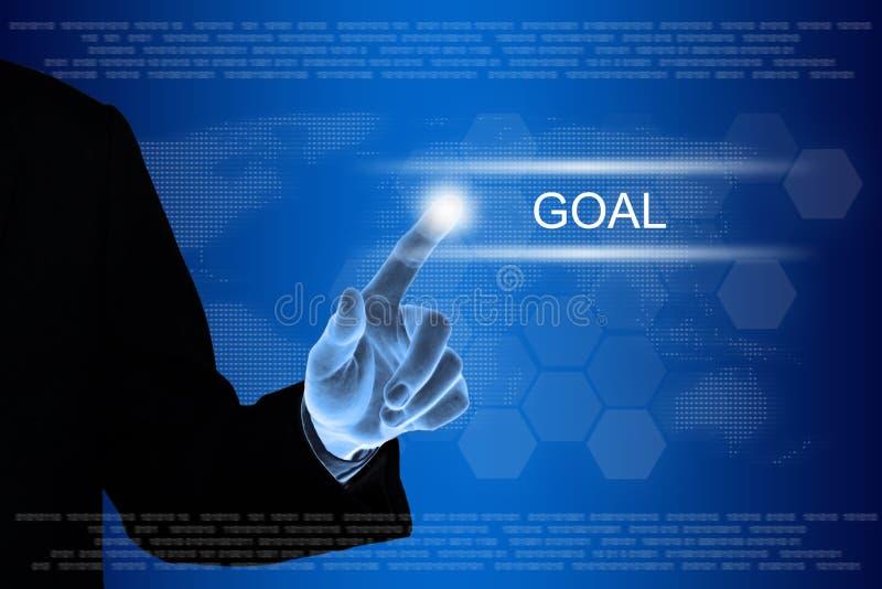 Mano del negocio que hace clic el botón de la meta en la pantalla táctil foto de archivo libre de regalías