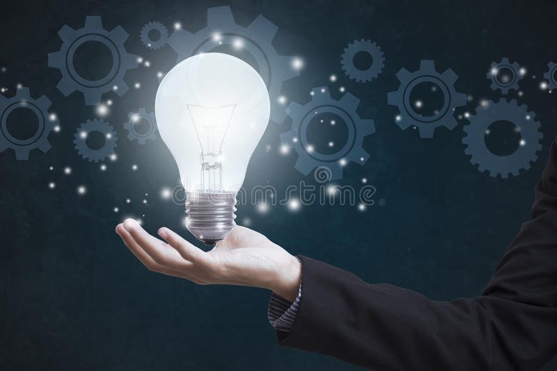 Mano del negocio que sostiene el bulbo de la luz eléctrica con las ruedas de engranaje imagen de archivo libre de regalías