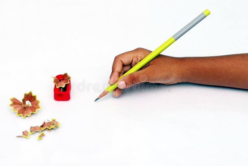 Mano del niño con el lápiz y los sacapuntas imagen de archivo