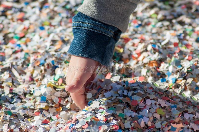 mano del niño pequeño que juega con la pila del confeti en la calle fotografía de archivo