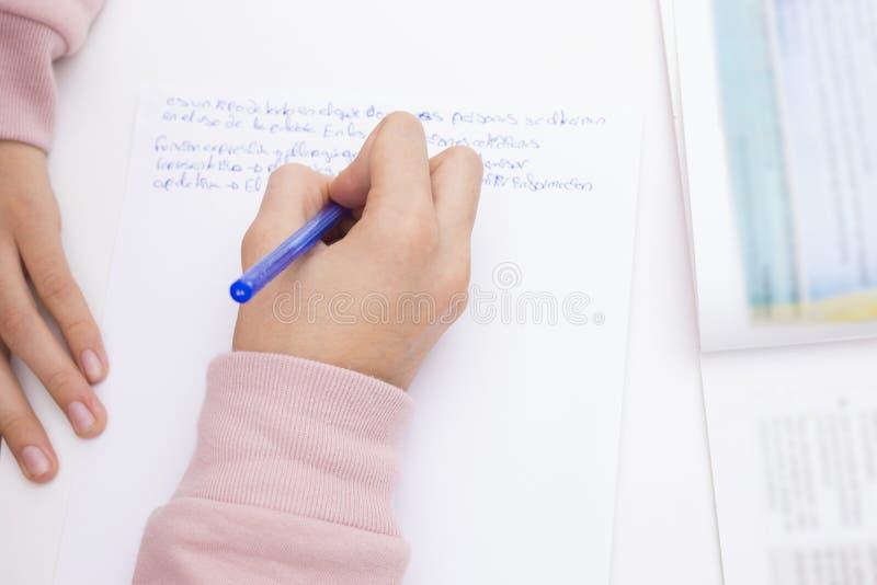 Mano del niño que estudia y que escribe imagenes de archivo